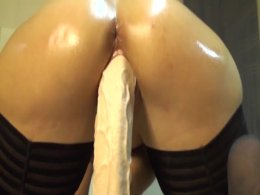 Stunning ass chick oils herself up and rides a massive dildo