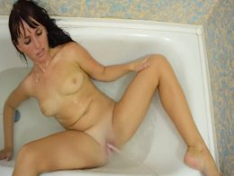 Stream of water makes this brunette's shaved pussy cum hard