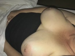MILF with big boobs making herself cum under the bed sheets